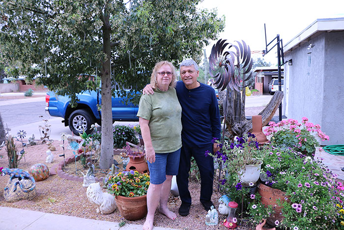 A senior couple stand in their front yard among pots of lowering annuals, wind chimes and other garden décor.