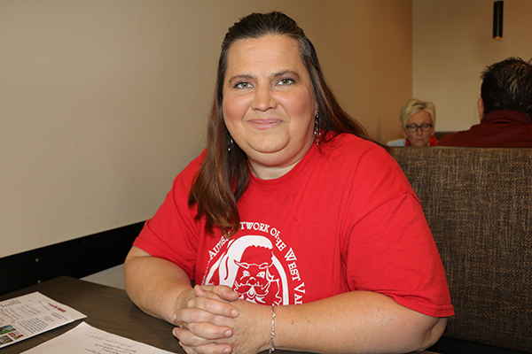 woman sits at a table, smiling at the camera