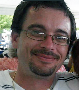 A White male with brown eyes, brown hair, mustache and goatee, wearing glasses.