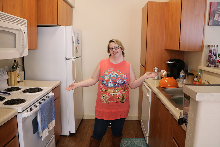 Young woman expands her arms out to showcase her kitchen.