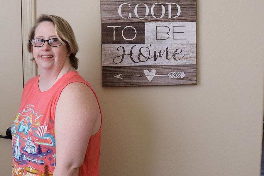 Young woman stands by wall art that reads:  It is so good to be home.