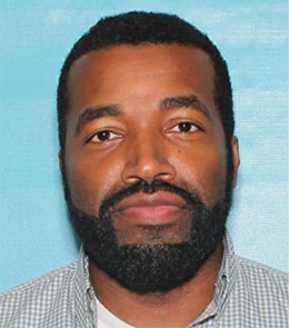 A Black male with brown eyes, brown hair, mustache and beard.