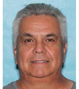 Hispanic man with white, slicked-back hair wearing grey t-shirt