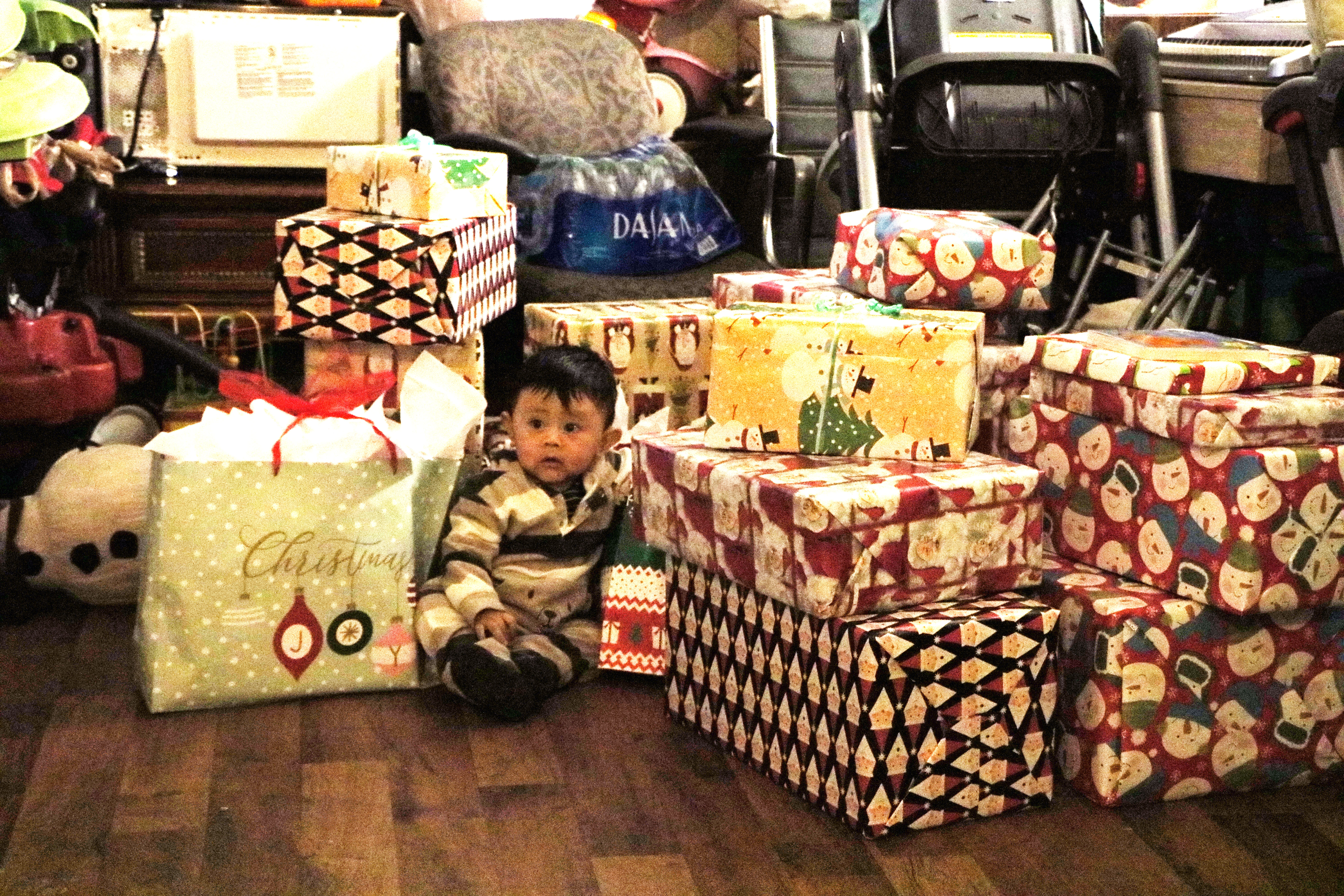 Toddler sits on floor among a stack of holiday presents