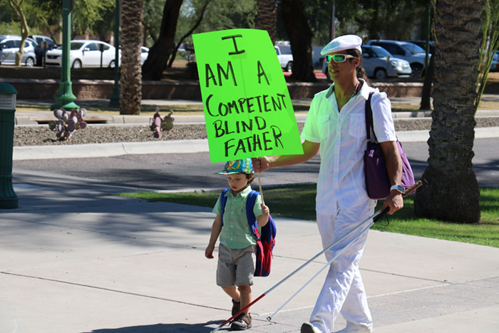 "A blind man holds a sign that says ""I am a competent blind father"" as he walks with his young son"