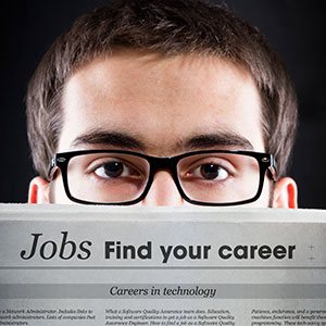 A Young Man Reads A News Article Titled Jobs Find Your Career