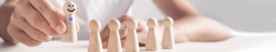 a hand selects a wooden figure from a group of others