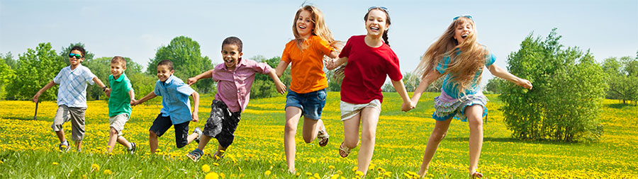 a group of children running in a field of flowers