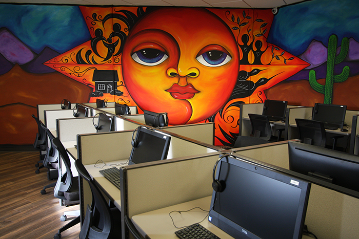 a computer lab; a mural of a bright desert scene is visible on a wall