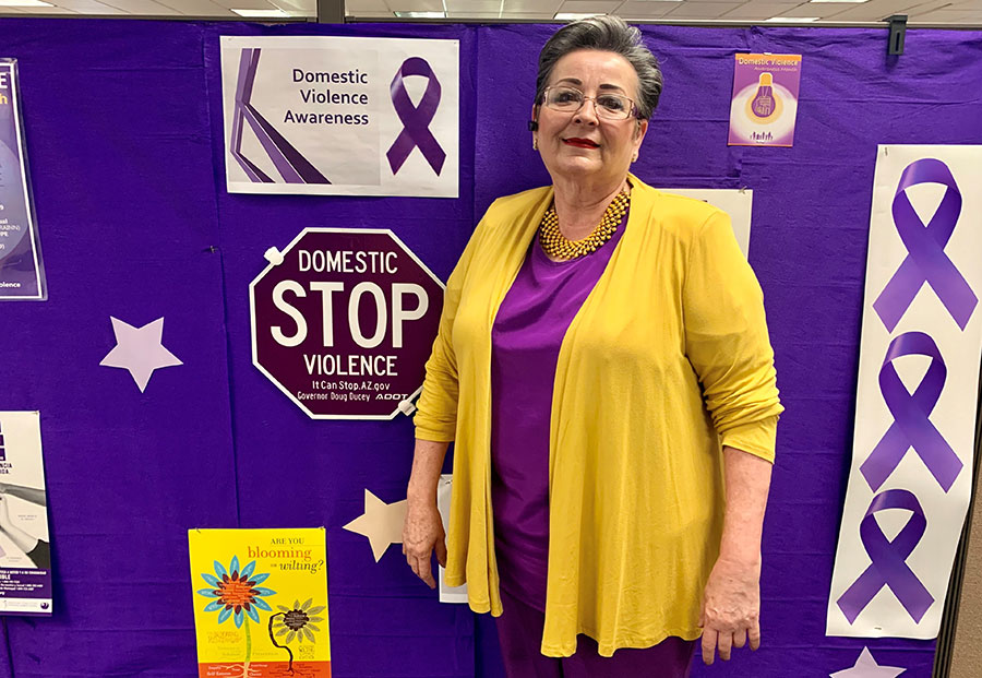 a woman dressed in yellow and purple poses for a photo; behind her, Domestic Violence awareness paraphernalia display on a purple wall