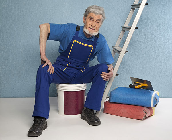 elderly man with a ladder and bucket and other construction equipment