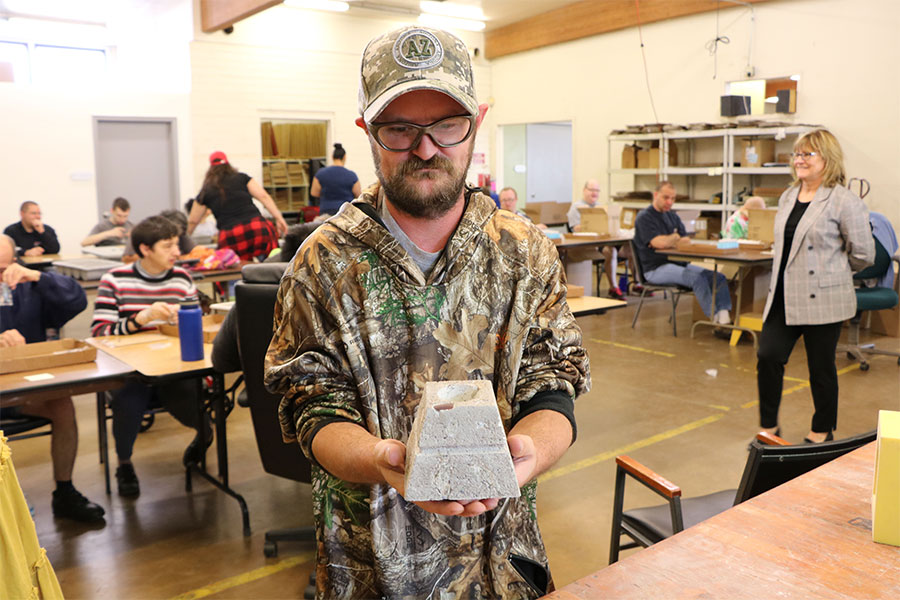 Man in camouflage shirt and hat holds up a sample of a candle block made at a vocational center.
