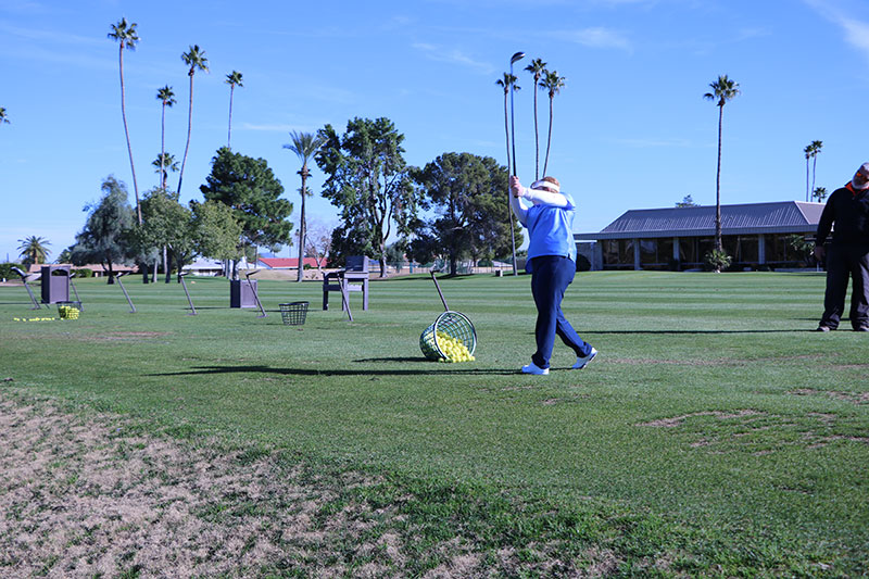 Female collegiate athlete drives a golf ball toward the green.