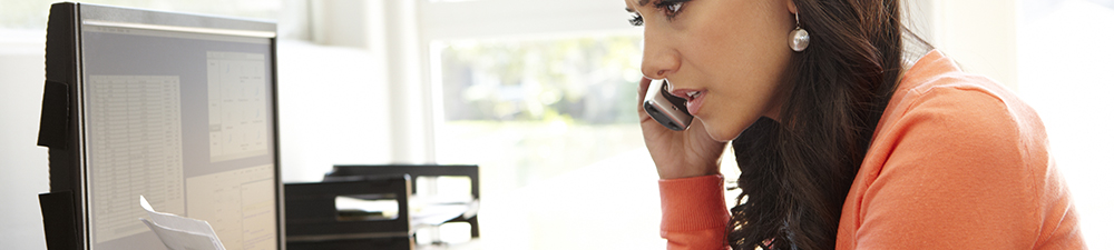 Concerned young woman reviewing document and talking on the telephone.