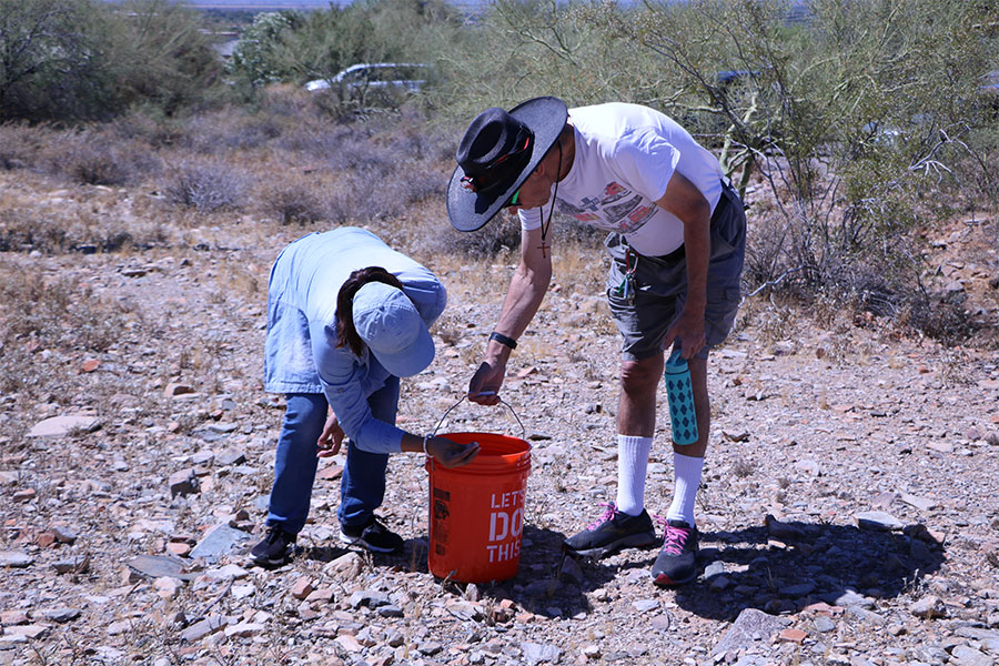 Man wearing a hat holds a bucket for a woman leaning down to pick up a rock.