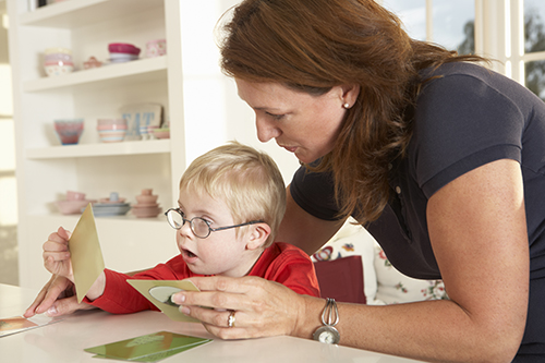Female therapist working with young boy with developmental disability at a table.