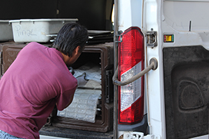 a man is removing packages from the back of a van