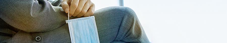 un hombre en traje de negocios está sentado, sosteniendo un cubrebocas en la mano