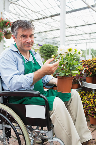 Man in a wheelchair works as a gardener