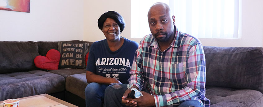 A mother sits with her adult son on the living room couch.