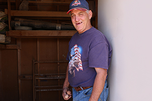 Middle-aged man wearing ball cap, T-shirt and blue jeans stands in the doorway of a chick house with two eggs in his right hand