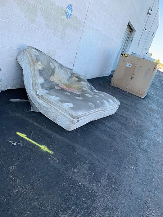 an old mattress leans against a wall