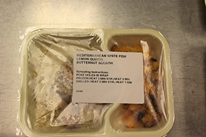 "a packaged meal with label on top that reads ""Mediterranean White Fish, Lemon Quinoa, Butternut Squash"""