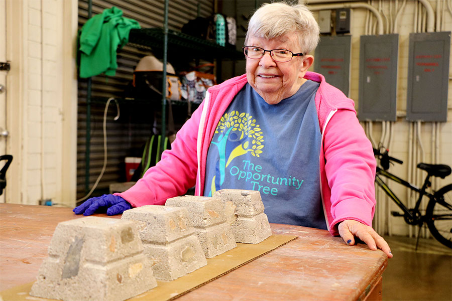 Woman in a pink jacket stands behind a row of four recently made candle blocks.