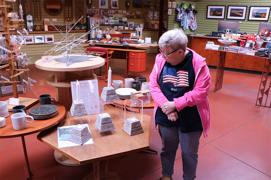 Woman in a pink jacket stands next to a display of table décor in a retail gift shop.