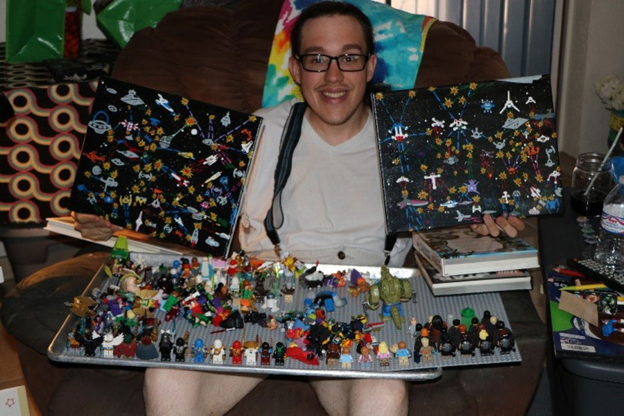 a man wearing glasses holds up in each hand a work of art that is space-themed. In his lap is a tray of lego figures