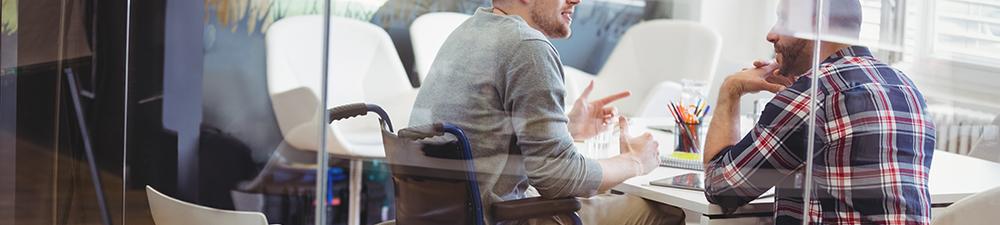 Hombre discapacitado en silla de ruedas en el trabajo que habla con un compañero de trabajo sentado en una mesa.