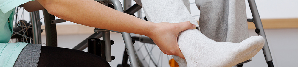Nurse assisting a wheelchair bound man with leg exercises.