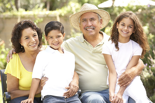 senior citizen male and female sitting on bench holding young male and female children