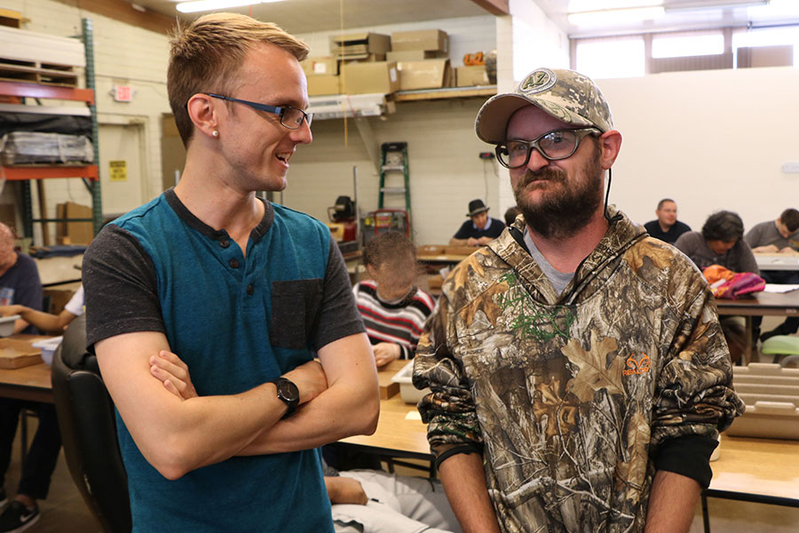 Two man stand side-by-side in front of other workers at a vocational center.