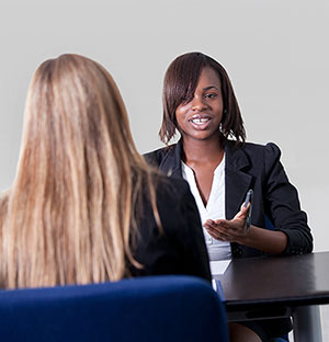 two women dressed in business attire sit across a table from each other talking