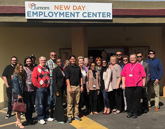 "a group of people stand in front a building with a sign that reads ""UMOM New Day Employment Center"""