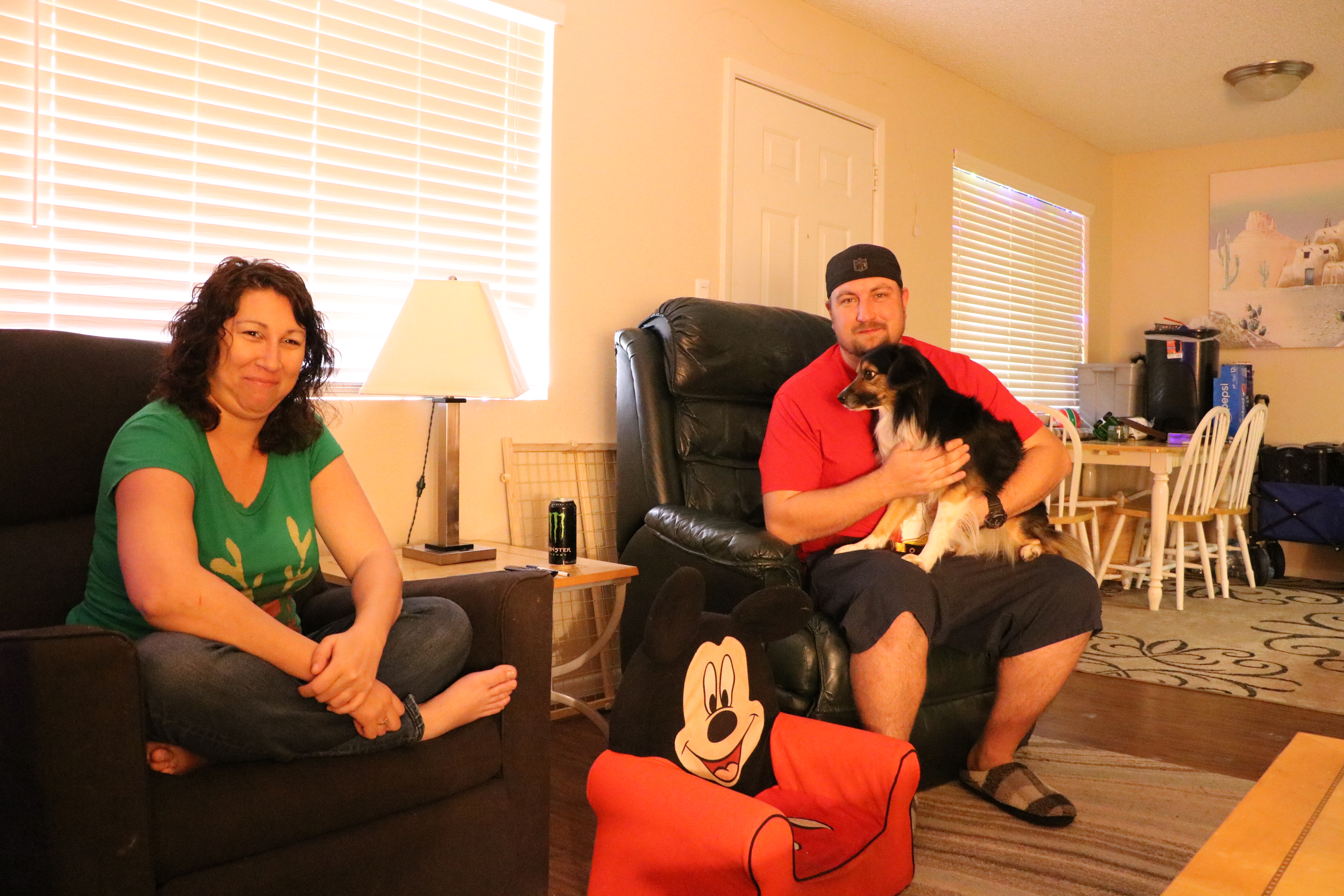 Woman and man sitting in chairs.  Man holds the family dog in his lap