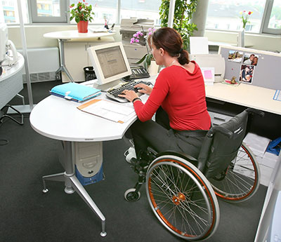 woman sitting in wheelchair works on a computer at desk