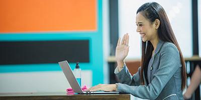 """woman waving """"hello"""" at laptop screen"""