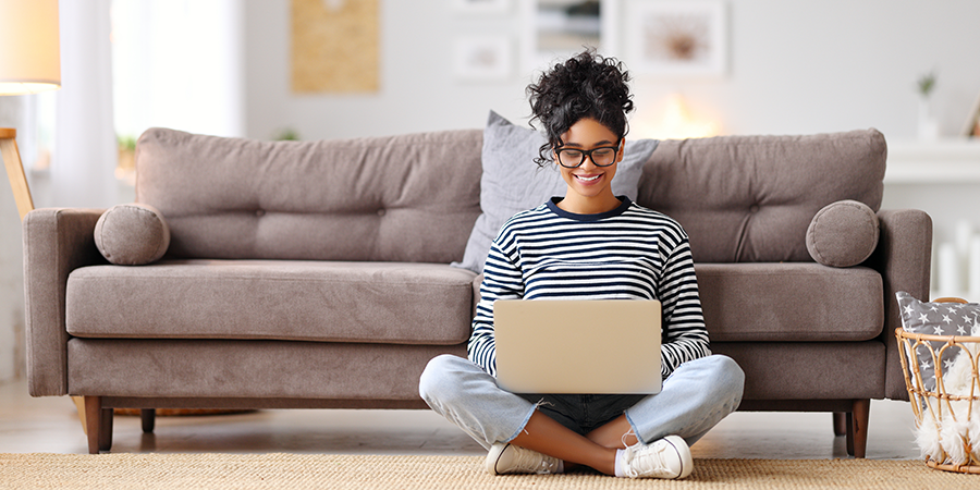 a young woman sits on the floor, in front of a sofa, working on a laptop computer