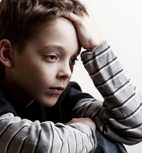Child leaning forward with hand to forehead