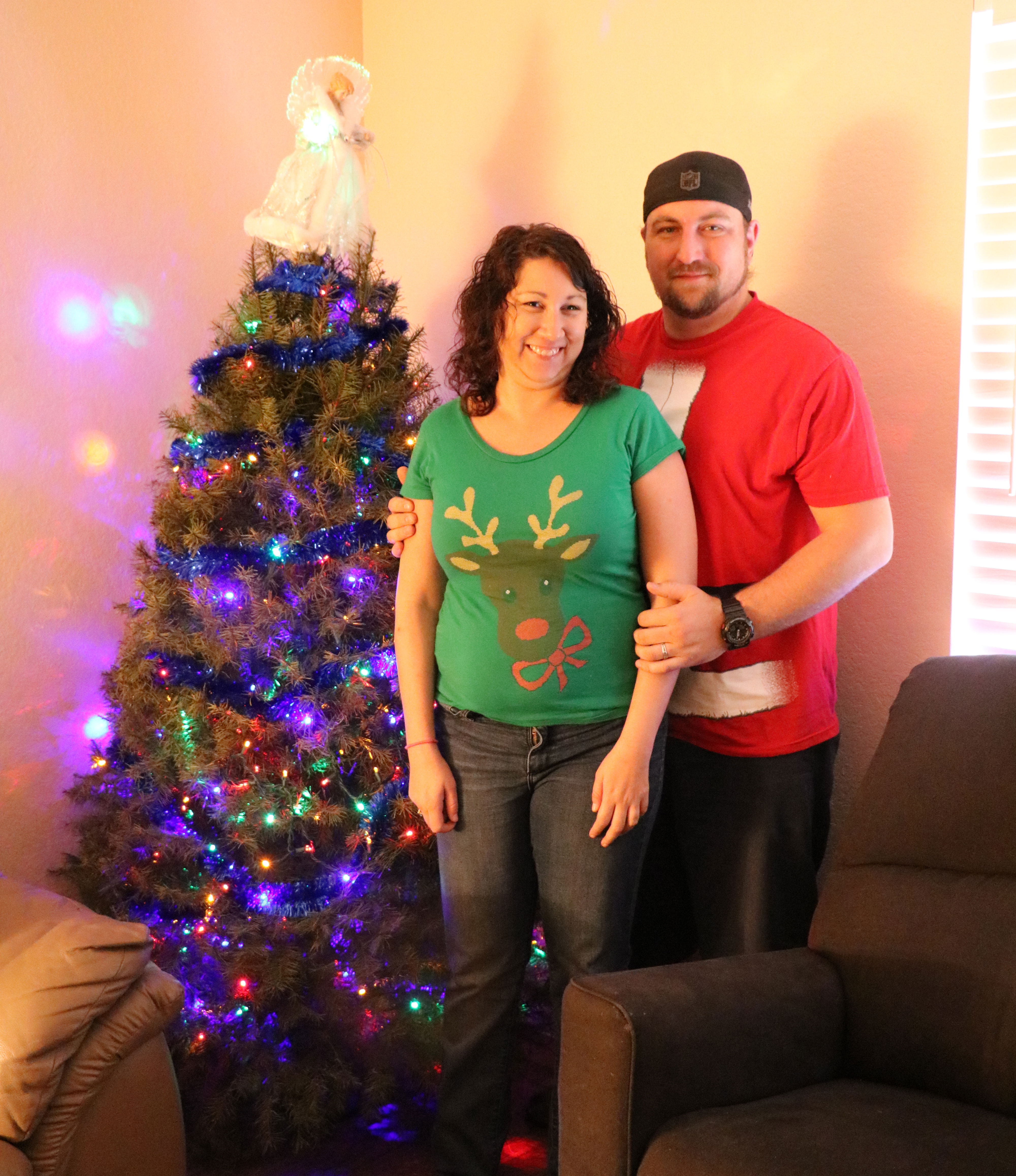 Young couple pose for a photo by their decorated Christmas tree