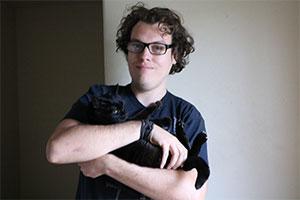A young man cradles a black cat