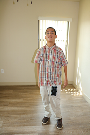 Young man stands in the center of an empty room that he selected as his new bedroom.