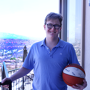Young man stands on the backyard balcony cradling a basketball in his left hand.