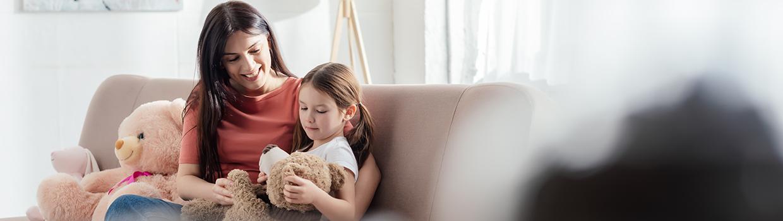 mom girl on sofa with teddy bear