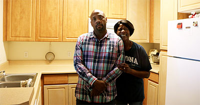 Man with his mother standing in the kitchen of their apartment home.