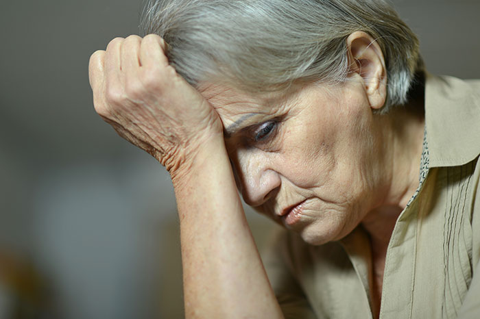 older, sad woman touching her palm to her forehead
