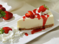 a slice of cheesecake topped with whip cream and fresh strawberries