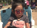 a little girl wearing sunglasses sits in a go cart with her hand on the steering wheel